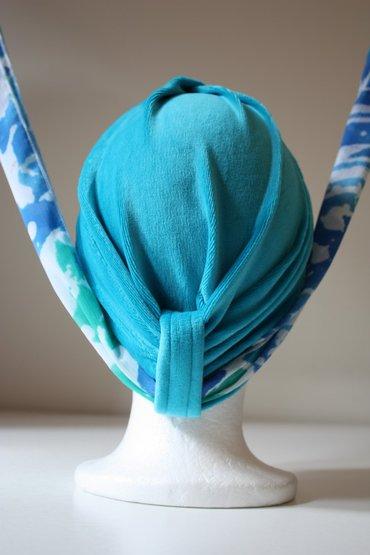 Stap 1: Doe de muts op en haal het sjaaltje door de lus achter op je hoofd.
